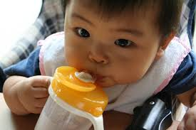 マグを使って上手に飲み物を飲む赤ちゃん