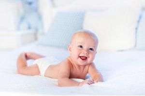 赤ちゃんが布団の上でずりばいしているところ